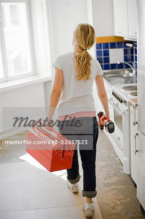 Woman with toolbox and screwdriver from behind Stock Photo - Premium Royalty-Free, Image code: 698-03657523