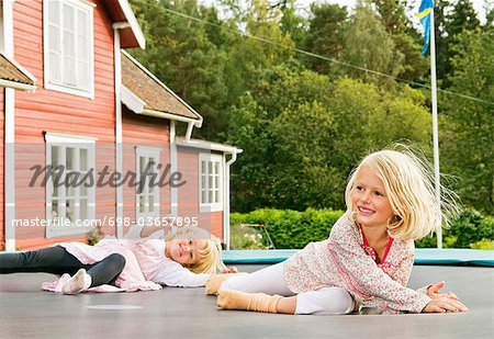 Two sisters lying on rebouncer Stock Photo - Premium Royalty-Free, Image code: 698-03657895