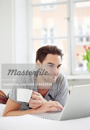 Man with coffee and computer Stock Photo - Premium Royalty-Free, Image code: 698-03658310