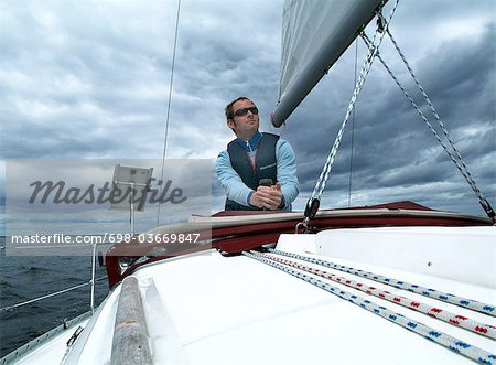 Man on sailboat Stock Photo - Premium Royalty-Free, Image code: 698-03669847