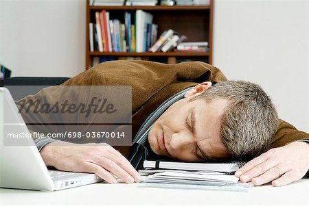 Man has fallen asleep on the desk Stock Photo - Premium Royalty-Free, Image code: 698-03670014