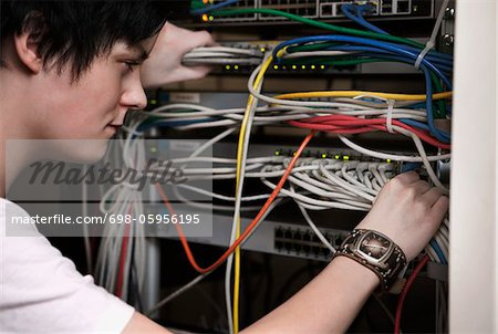 Woman pulling network cables Stock Photo - Premium Royalty-Free, Image code: 698-05956195