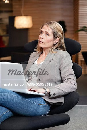 Woman on chair with laptop Stock Photo - Premium Royalty-Free, Image code: 698-05956348