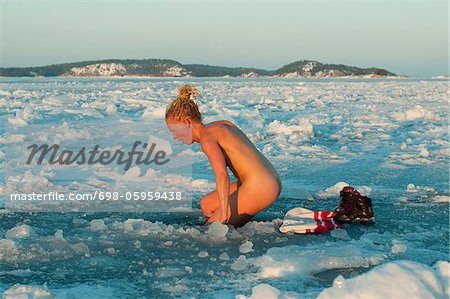 Woman bathing naked in ice hole Stock Photo - Premium Royalty-Free, Image code: 698-05959438