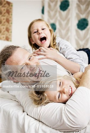 father having fun with his daughters Stock Photo - Premium Royalty-Free, Image code: 698-05959518