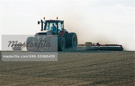 Farmer plowing field with tractor Stock Photo - Premium Royalty-Free, Image code: 698-05980439