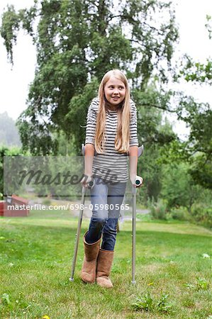 Physically impaired girl with crutches looking away Stock Photo - Premium Royalty-Free, Image code: 698-05980565