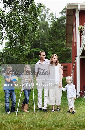 Family with three children standing in back yard Stock Photo - Premium Royalty-Free, Image code: 698-05980566