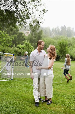 Couple looking at each other with children playing in background Stock Photo - Premium Royalty-Free, Image code: 698-05980568