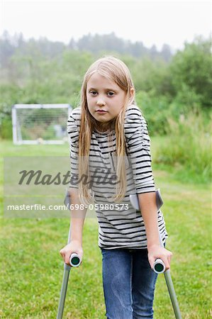 Portrait of girl with crutches in sad mood Stock Photo - Premium Royalty-Free, Image code: 698-05980573