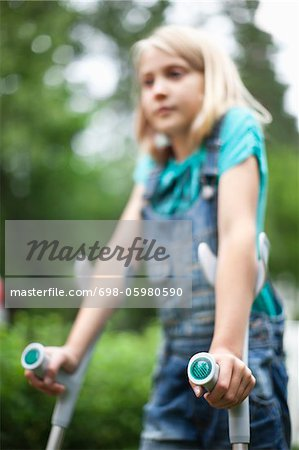 Physically impaired girl with focus on crutches Stock Photo - Premium Royalty-Free, Image code: 698-05980590