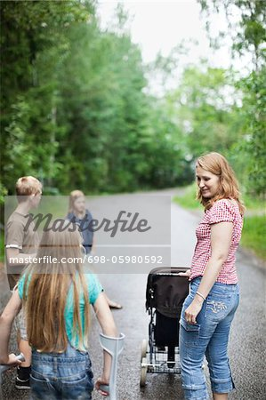 Mother with three children walking on road in forest Stock Photo - Premium Royalty-Free, Image code: 698-05980592