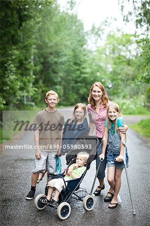 Portrait of mother with children standing on road in forest Stock Photo - Premium Royalty-Free, Image code: 698-05980593