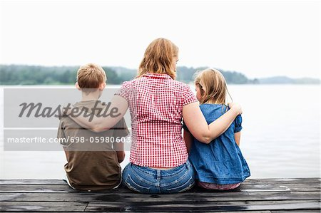 Rear view of mother with arm around her children sitting on pier Stock Photo - Premium Royalty-Free, Image code: 698-05980603