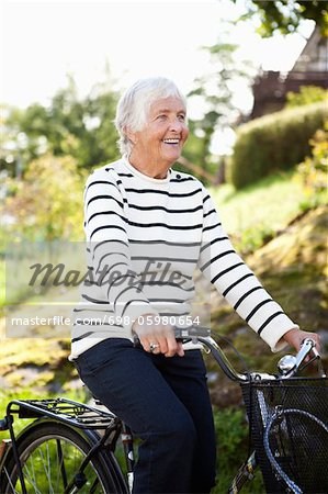 Happy senior woman cycling in park Stock Photo - Premium Royalty-Free, Image code: 698-05980654
