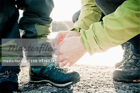 Father helping boy tie his shoe lace Stock Photo - Premium Royalty-Free, Image code: 698-05980792