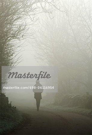 Person walking on a foggy country road Stock Photo - Premium Royalty-Free, Image code: 698-06116954