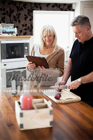 Couple in kitchen using digital tablet for recipe and cooking meal Stock Photo - Premium Royalty-Free, Image code: 698-06117283
