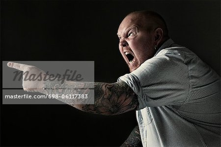 Side view of a furious mature man shouting while pointing over black background Stock Photo - Premium Royalty-Free, Image code: 698-06117383