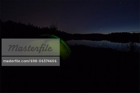 Dome tent on camping site near lake in forest Stock Photo - Premium Royalty-Free, Image code: 698-06374606