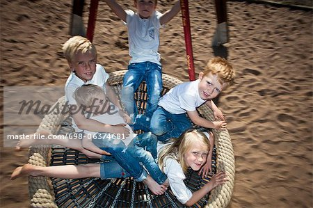 High angle view of happy children swinging in garden Stock Photo - Premium Royalty-Free, Image code: 698-06374681
