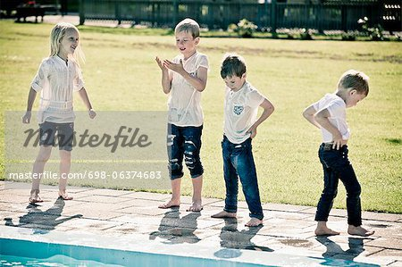 Full length of four children standing by swimming pool Stock Photo - Premium Royalty-Free, Image code: 698-06374683