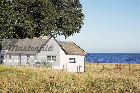 Tranquil scene of house with sea in background Stock Photo - Premium Royalty-Free, Image code: 698-06374800