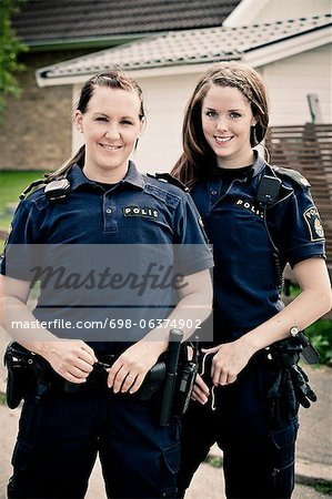 Portrait of two female police officers standing together Stock Photo - Premium Royalty-Free, Image code: 698-06374902