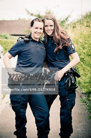 Portrait of two female police officers standing together Stock Photo - Premium Royalty-Free, Image code: 698-06374908