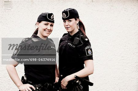 Portrait of two female police officers standing together Stock Photo - Premium Royalty-Free, Image code: 698-06374916