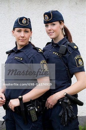 Portrait of two confident female police officers standing together Stock Photo - Premium Royalty-Free, Image code: 698-06374919
