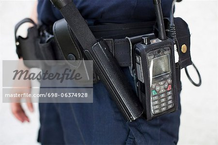 Midsection of a police officer with walkie-talkie and night stick on equipment belt Stock Photo - Premium Royalty-Free, Image code: 698-06374928