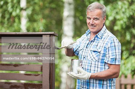 Portrait of a happy senior man painting wood in yard Stock Photo - Premium Royalty-Free, Image code: 698-06374954