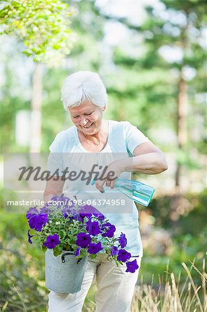 Happy senior woman spraying water on flower plant Stock Photo - Premium Royalty-Free, Image code: 698-06374958
