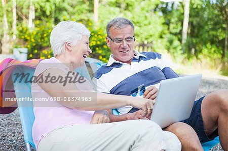 Happy senior couple shopping online together while relaxing on lounge chairs Stock Photo - Premium Royalty-Free, Image code: 698-06374963