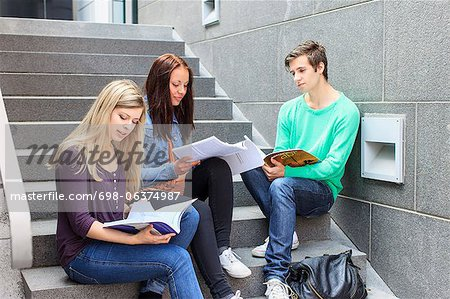 Young students studying on steps in university Stock Photo - Premium Royalty-Free, Image code: 698-06374987