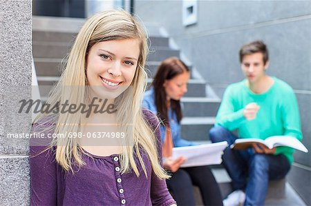 Portrait of a young female student with friends studying on steps in the background Stock Photo - Premium Royalty-Free, Image code: 698-06374989