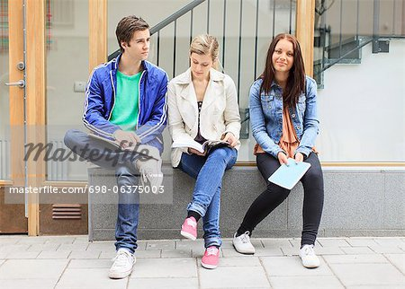 Young friends with books sitting on stone bench in university campus Stock Photo - Premium Royalty-Free, Image code: 698-06375003