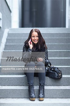 Portrait of a young female student using cell phone while sitting on steps Stock Photo - Premium Royalty-Free, Image code: 698-06375021