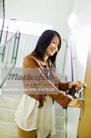 Mid adult woman unlocking door with keys Stock Photo - Premium Royalty-Free, Image code: 698-06375134
