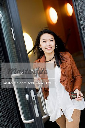 Portrait of a mid adult woman exiting through glass door Stock Photo - Premium Royalty-Free, Image code: 698-06375139