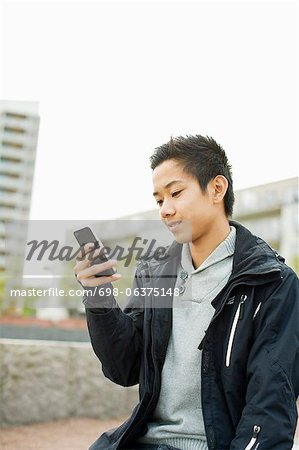 Teenage boy using smart phone Stock Photo - Premium Royalty-Free, Image code: 698-06375148