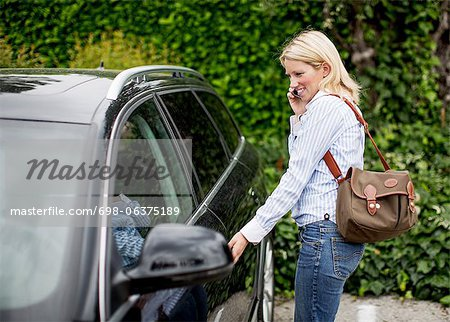 Mid adult woman using mobile phone while opening car door Stock Photo - Premium Royalty-Free, Image code: 698-06375189