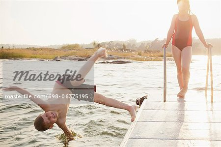 Little boy jumping in water with sister standing on pier Stock Photo - Premium Royalty-Free, Image code: 698-06375195