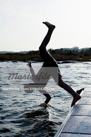 Silhouette of a little boy diving into water Stock Photo - Premium Royalty-Free, Image code: 698-06375196