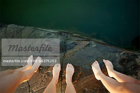 Low section of three people standing on cliff Stock Photo - Premium Royalty-Free, Image code: 698-06375202