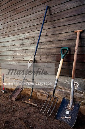 Group of gardening tools against wooden wall Stock Photo - Premium Royalty-Free, Image code: 698-06375209