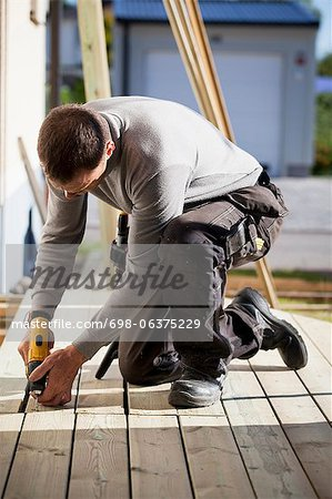 Manual worker drilling nail on floorboard Stock Photo - Premium Royalty-Free, Image code: 698-06375229