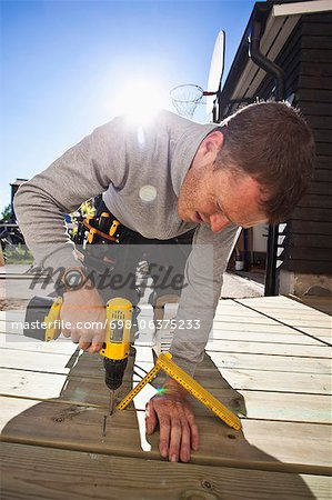 Manual worker drilling nail on floorboard against sunbeam Stock Photo - Premium Royalty-Free, Image code: 698-06375233