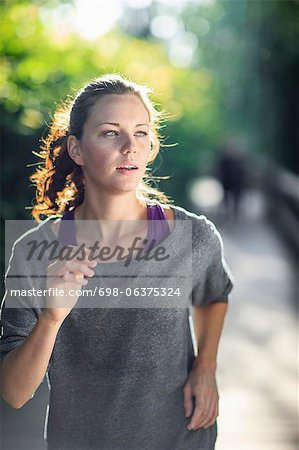 Young woman looking away as she jogs Stock Photo - Premium Royalty-Free, Image code: 698-06375324